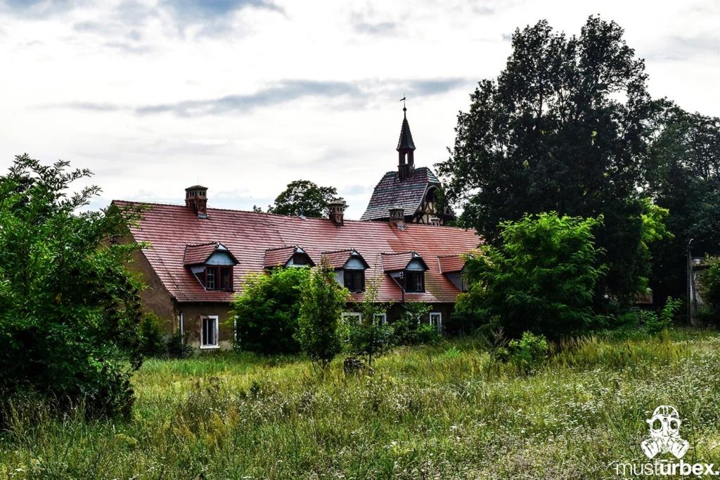 Malowniczy dwór - pałac w Osłej na Dolnym Śląsku, Osła 62, Dolny Śląsk - dwór z kogutkiem na tle drzew