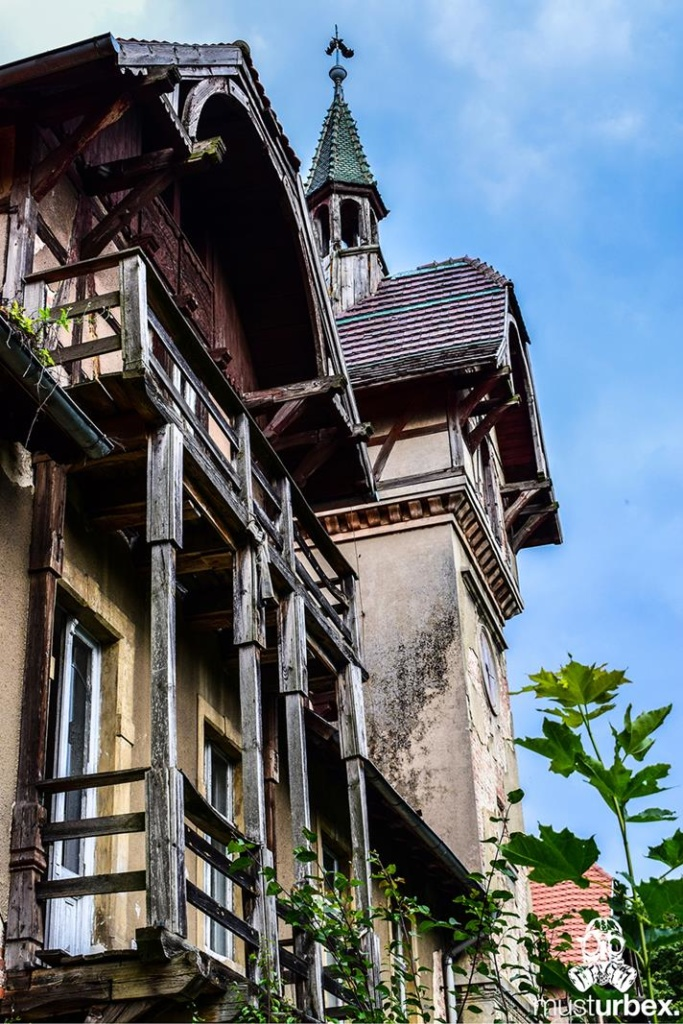 Malowniczy dwór - pałac w Osłej na Dolnym Śląsku, Osła 62, Dolny Śląsk - drewniany balkon, w tle wieza z kogutkiem