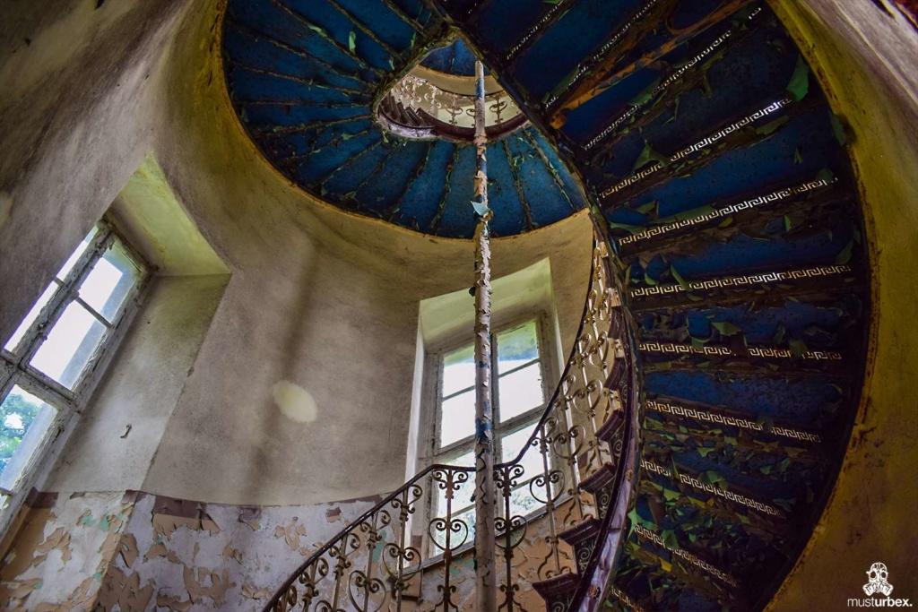 Opuszczony pałac z niebieskimi schodami urbex musturbex abandoned Palace with blue stairs Palast mit blauen Treppen Palác s modrými schody klatka schodowa odpadajaca farba niebieska farba błękit poręcz balustrada stopnie okna wieża