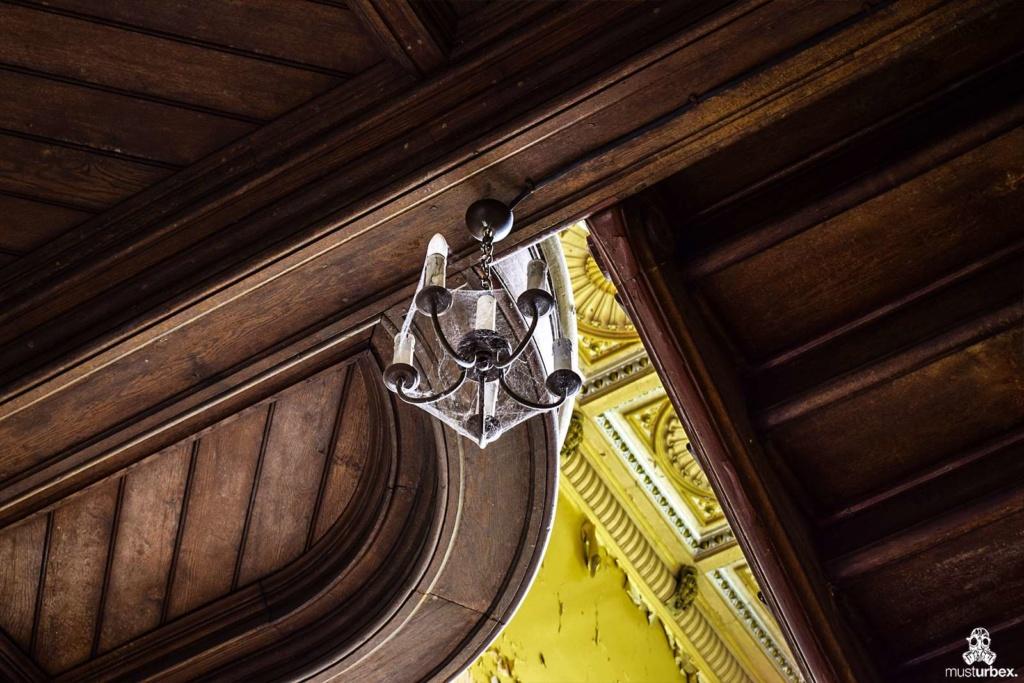 Opuszczony pałac z niebieskimi schodami urbex musturbex abandoned Palace with blue stairs Palast mit blauen Treppen Palác s modrými schody pajęczyna żyrandol lampa oświetlenie drewno drewniany sttrop sufit